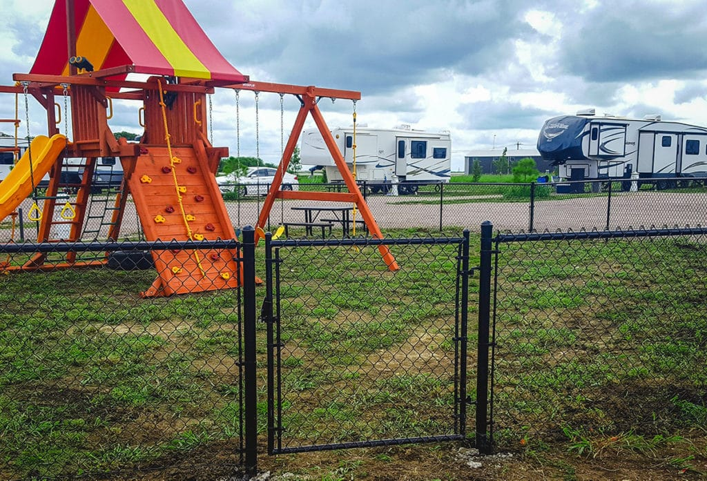 Vinyl chain link fence with walk gate securing a playground.